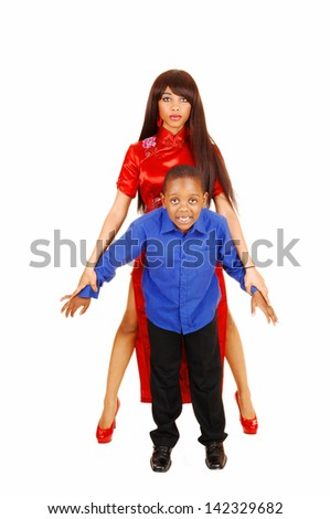 A teenage sister in a red dress holding her little brother in front of her on white background.  - stock photo