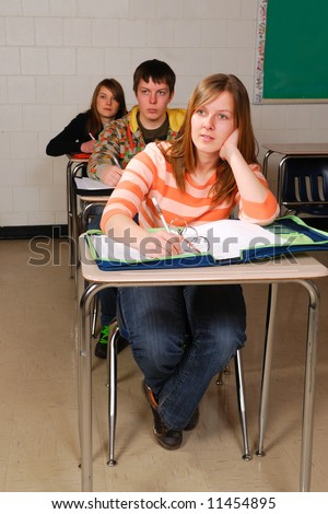 A teenage student listens in high school class - stock photo