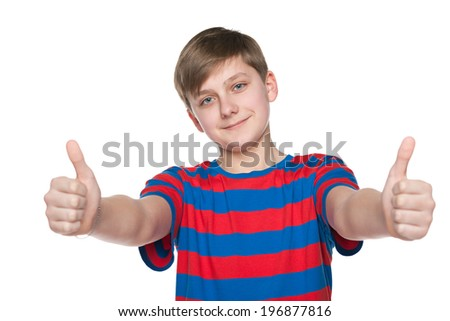 A teenager boy holds his thumbs up on the white background - stock photo