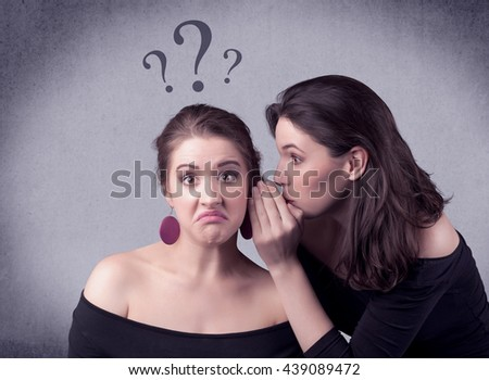 A teenager girl looking confused with drawn question marks above the head, while a girlfriend whispers something in her ear concept. - stock photo