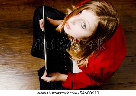a teenager girl looking up from her laptop - stock photo