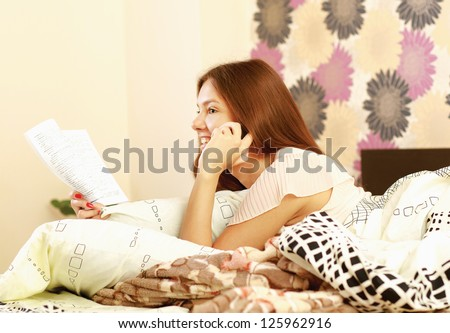 A teenager girl lying on a bed reading a book and talking on a mobile phone at the same time - stock photo