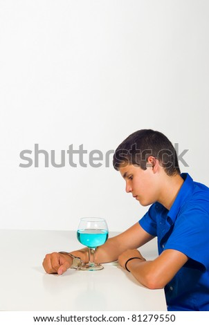 A teenager handcuffed to a cocktail glass, an alcoholism concept - stock photo