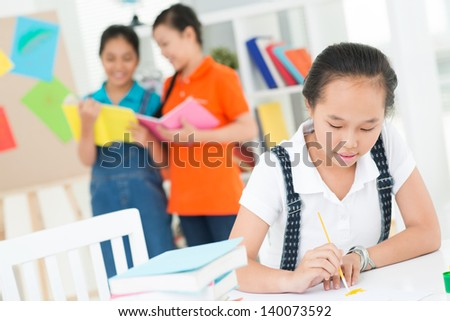 A teenager holding a brush at the art lesson on the foreground - stock photo