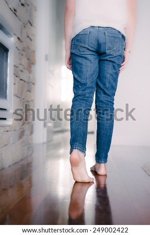 a teenager in jeans at home, walking away from camera - stock photo