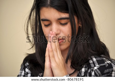 A teenager prays usually in her quiet bedroom - stock photo