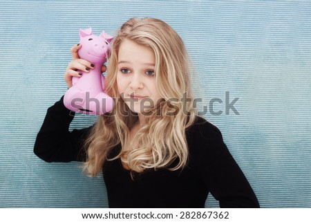 A teenager shaking her savings box with money - stock photo