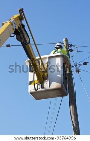 A Telecom/Electrical Engineer using a Mobile Elevating Work Platform Machine. - stock photo