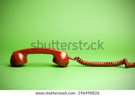 A telephone receiver and cord lying face down. - stock photo