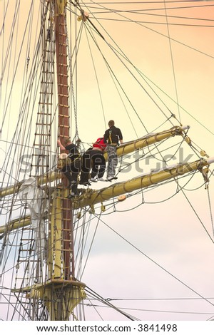 A telephoto of sailors at an old, tall sailing boat