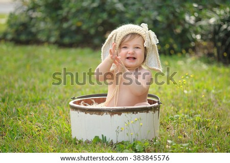 A ten month old baby girl wearing a tan, crocheted, bunny bonnet. She is sitting in a white, wooden bucket, smiling and clapping her hands. Shot outdoors with green grass and shrubs. - stock photo