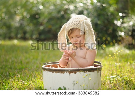 A ten month old baby girl wearing a tan, crocheted, bunny bonnet. She is sitting in a white, wooden bucket and looking down at her hands. Shot outdoors with green grass and backlighting. - stock photo