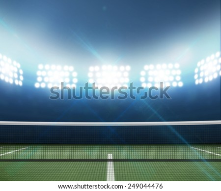 A tennis court in an arena with a marked green hard surface at night under illuminated floodlights - stock photo