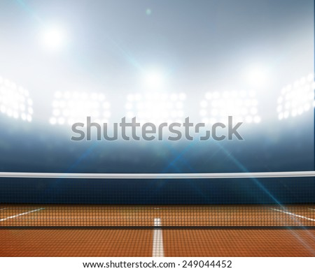A tennis court in an arena with a marked orange clay surface at night under illuminated floodlights - stock photo