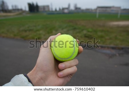 a tennis green ball in hand against the background of a sports field.