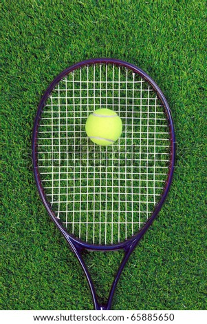 A tennis raquet or racket and yellow ball on grass. - stock photo
