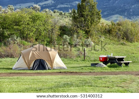 A tent and eating area set up at a campsite in a public campground in the mountains