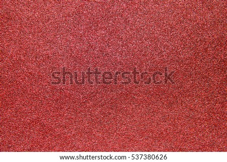 A texture of a coarse grit sandpaper