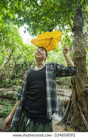 A Thai-Chinese man in standing post under the rain in the forest - stock photo