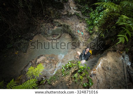 A Thai-Chinese teen playing in waterfall under the rain in deep forest - stock photo