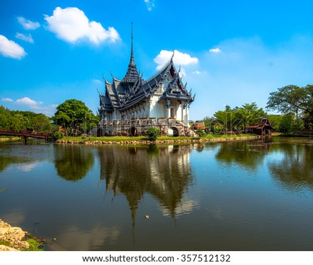 A Thai temple against a blue sky and reflection in a pond.