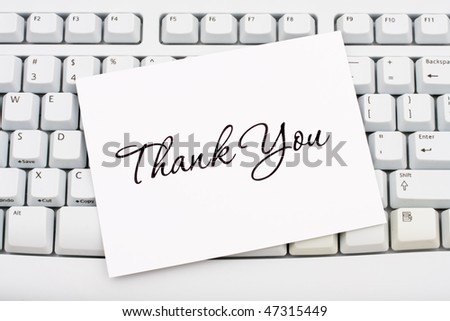 A thank you card sitting on a computer keyboard, online thank you - stock photo