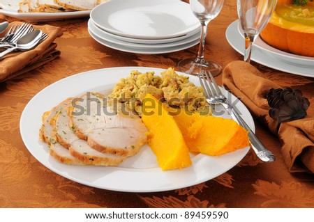 A Thanksgiving dinner table with a plate of turkey, butternut squash and dressing and a bowl of pumpkin soup