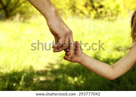 a the parent holding the hand of a small child