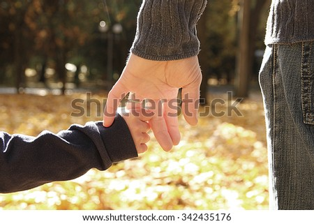 a the parent holds the hand of a little child in autumn park - stock photo
