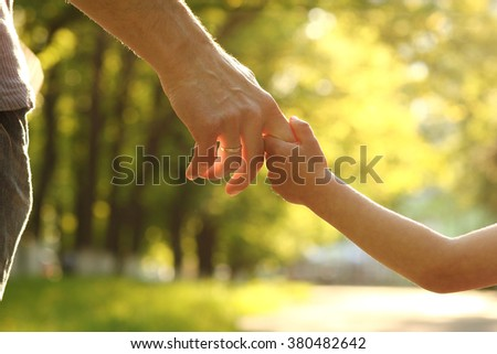 a the parent holds the hand of a small child - stock photo