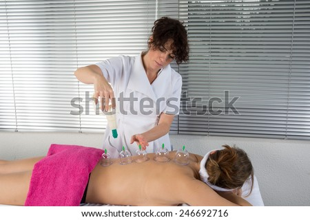 A therapist removing a glass globe in a fire cupping procedure - stock photo