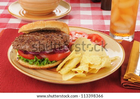 A thick hamburger with sour cream and chive potato chips