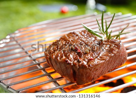 A thick strip steak being grilled outdoors - stock photo