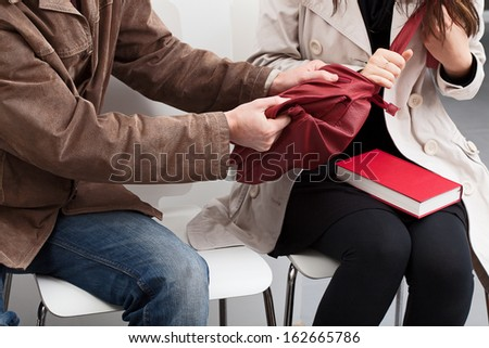 A thief and a woman yanking on her red bag - stock photo