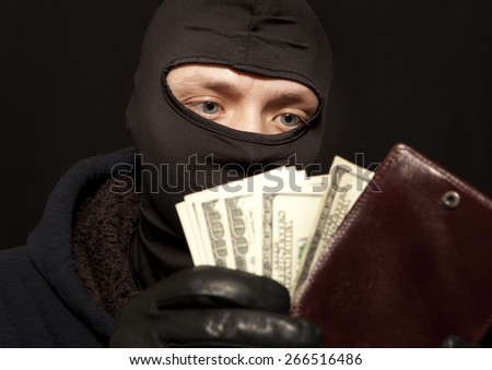 A thief sealing from a brown leather purse  - stock photo