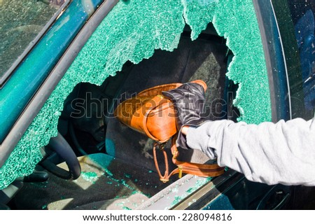a thief stole a purse from a car through a broken side window. - stock photo