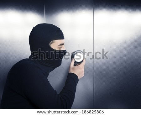 A thief tries to open a safe in a bank