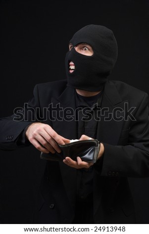 A thief wearing a balaclava snooping through a wallet, shot against a dark background