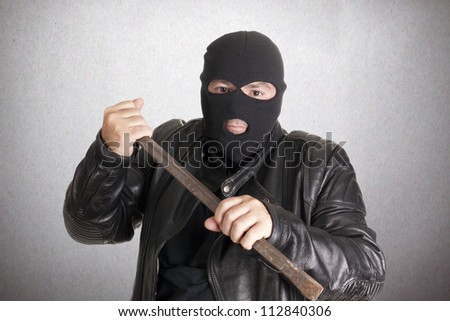 A thief with a crowbar to break into a house