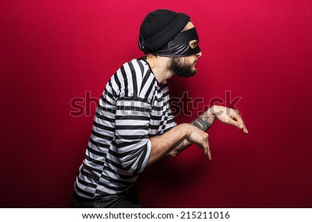 A thief with mask slinking on red background   - stock photo