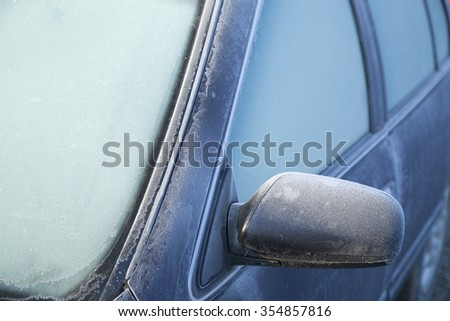 A thin film of icy frost covers this car - making the windshield too opaque to see through the window. Someone needs an ice scraper before they can start their morning commute.  - stock photo