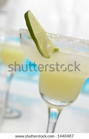 A thin lime slice in a margarita. Selective focus on edge of lime. - stock photo