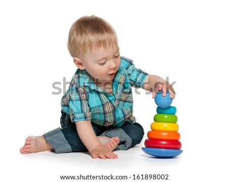 A thoughtful baby boy is playing with toys on the white background - stock photo