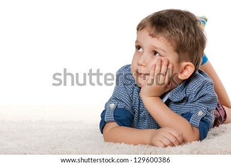 A thoughtful boy is dreaming on the white carpet - stock photo