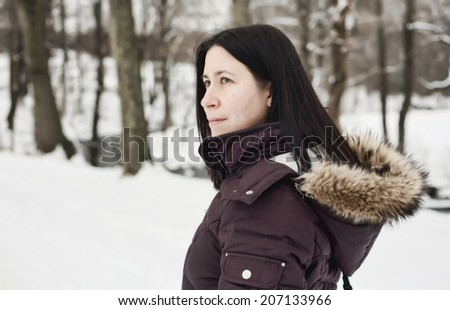 A thoughtful girl walks though a snowy forest. - stock photo