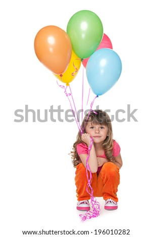 A thoughtful little girl holds balloons against the white background - stock photo