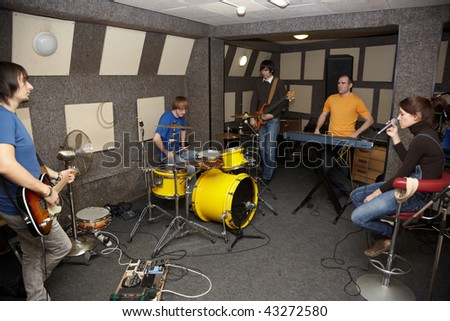 a thoughtful rock band. sad vocalist girl, two musicians with electrical guitars and one drummer working in studio. - stock photo