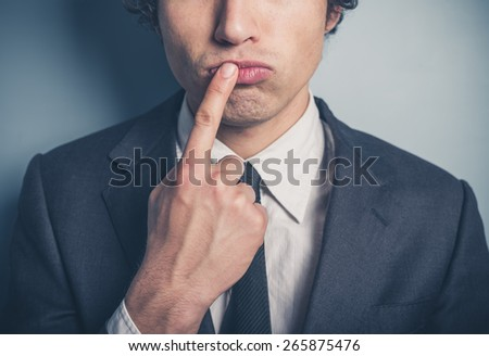 A thoughtful young businessman with his finger on his lips - stock photo