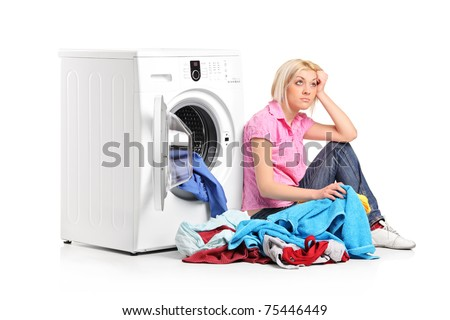 A thoughtful young woman with clothes seated next to a washing machine isolated on white background