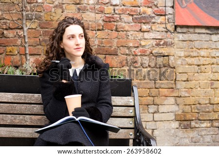 a thoughtful young woman with her diary and a coffee. - stock photo